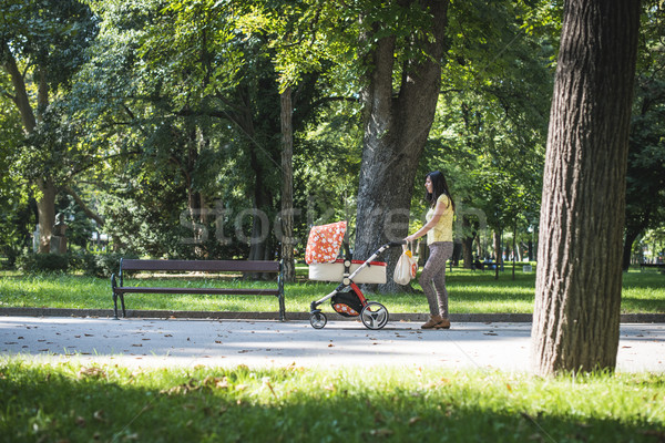 Mother walking in the park with baby buggy Stock photo © deyangeorgiev