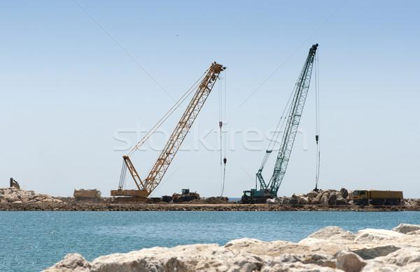 Building a dike. Cranes and excavator put stones Stock photo © deyangeorgiev
