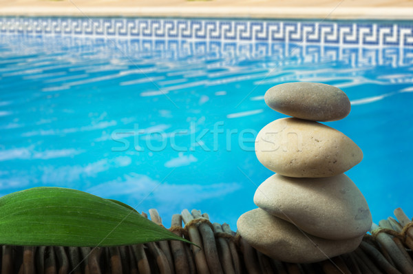 Stacked stones on wooden base for spa and green leaf Stock photo © deyangeorgiev