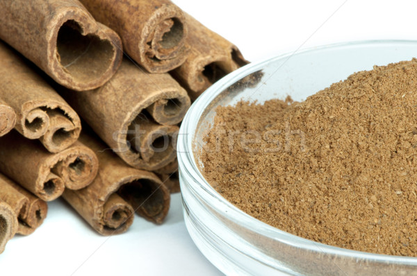 Powdered cinnamon in bowl and cinnamon sticks Stock photo © deyangeorgiev