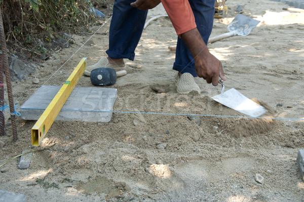 Worker puts sidewalk tiles Stock photo © deyangeorgiev