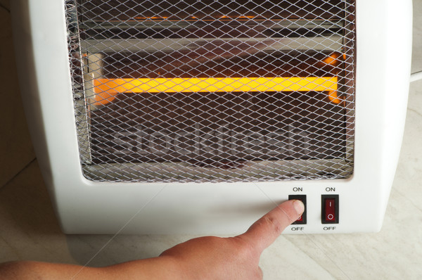 Electric heater and hand which includes switch Stock photo © deyangeorgiev