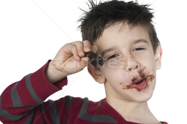 Sorridente pequeno menino alimentação chocolate criança Foto stock © deyangeorgiev