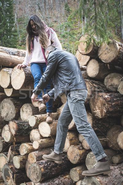 Young woman and men on wood logs Stock photo © deyangeorgiev