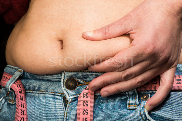 Woman showing fat belly Stock photo © deyangeorgiev