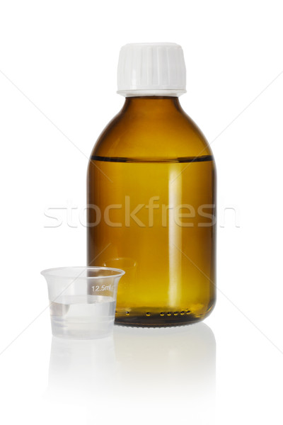 Medicine bottle and measuring cup  Stock photo © dezign56