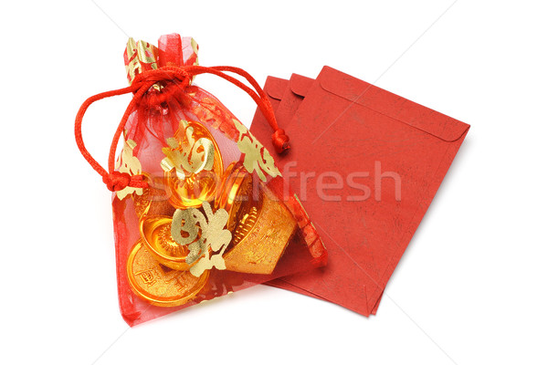 Gold ingots and coins in decorative sachet and red packets Stock photo © dezign56