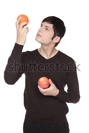 Stock photo: Caucasian man comparing apple to orange