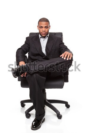 Stock photo: Young African American businessman relaxing in chair
