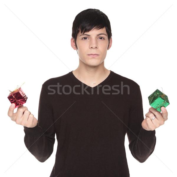 Caucasian man comparing green present to red Stock photo © dgilder
