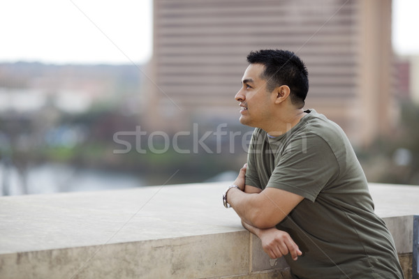 Hispanic Man - Looking out from balcony Stock photo © dgilder