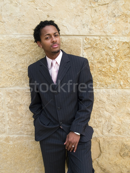 A businessman in a three piece suit looks at the camera as he leans against a stone wall. Stock photo © dgilder