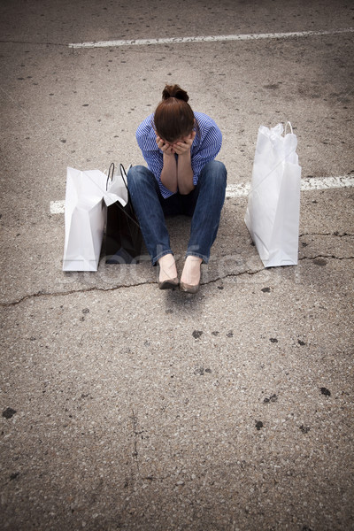lost woman sitting in parking lot with shopping bags covering fa Stock photo © dgilder