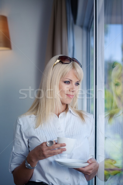 business woman drinking and staring out of window Stock photo © diego_cervo