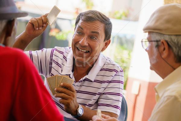 Groep gelukkig oude vrienden speelkaarten lachend Stockfoto © diego_cervo