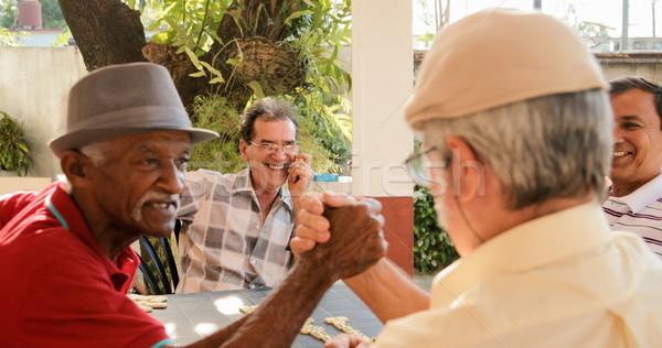 Oude mannen handen schudden winnend spel domino Stockfoto © diego_cervo