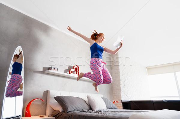 Una buona notizia felice ragazza jumping letto Foto d'archivio © diego_cervo