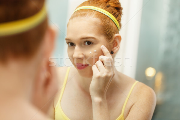 Young Woman Applies Anti-Aging Cream Looking At Mirror Stock photo © diego_cervo