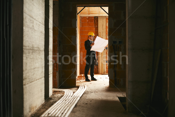 Architect standing in house under construction with building pla Stock photo © diego_cervo