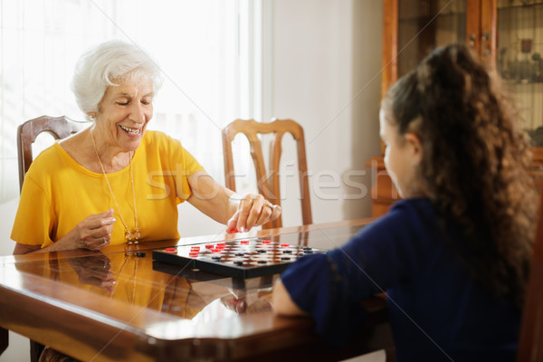 Grandma Playing Checkers Board Game With Granddaughter At Home Stock photo © diego_cervo