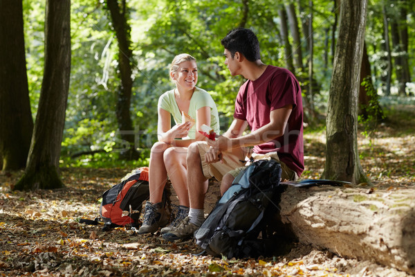 couple sitting on trunk and eating snack after trekking Stock photo © diego_cervo