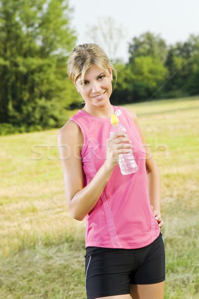Jogging fiatal nő ital vizes flakon kint sport Stock fotó © diego_cervo