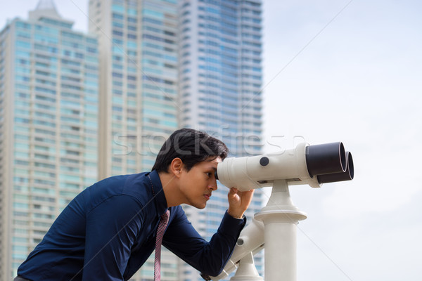 Asian business man with binoculars looking at city Stock photo © diego_cervo