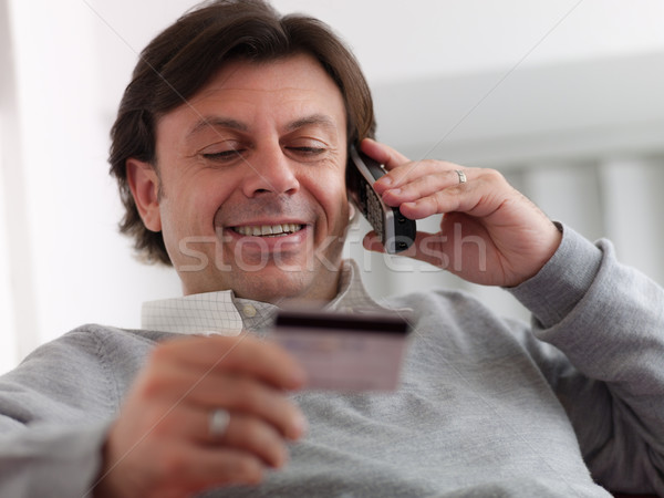 adult man shopping from home with telephone and credit card Stock photo © diego_cervo