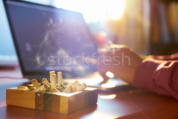 Man Using Laptop And Smoking Cigarette In Office Stock photo © diego_cervo
