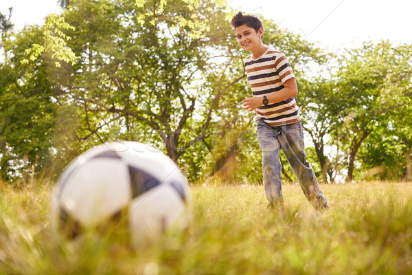 Young boy playing soccer game hitting ball Stock photo © diego_cervo