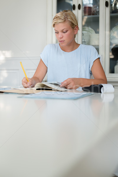 Stock photo: Young woman checking bills and doing budget at home