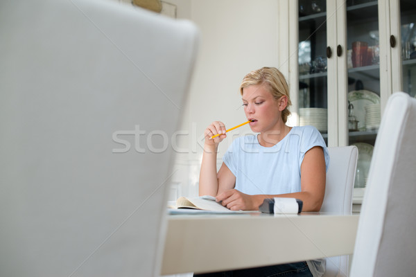 Young woman checking bills and doing budget at home Stock photo © diego_cervo