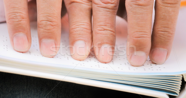 Fingers Of Blind Man Touching Page On Braille Book Stock photo © diego_cervo