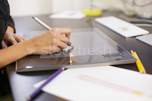Stock photo: Woman drawing sketches on computer in fashion design studio
