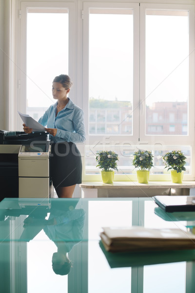 Young woman copying document with photocopy in office Stock photo © diego_cervo