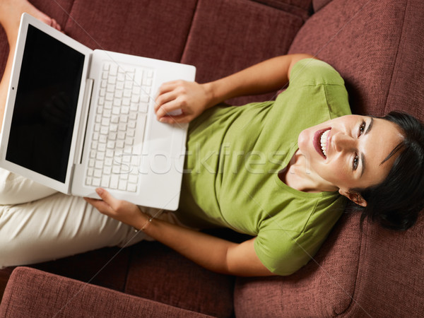 woman with pc laughing on sofa Stock photo © diego_cervo