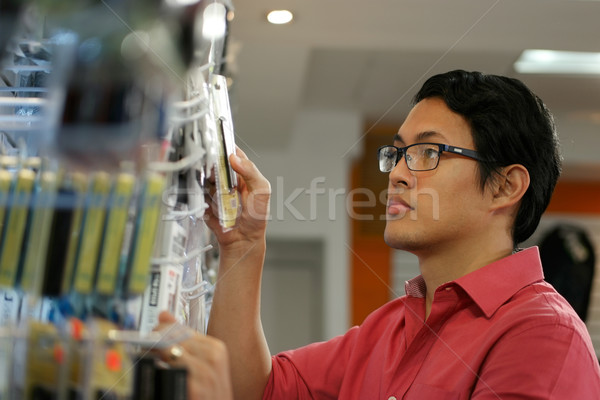 Chinese Man Ordering Usb Drive On Shelf In Computer Shop Stock photo © diego_cervo
