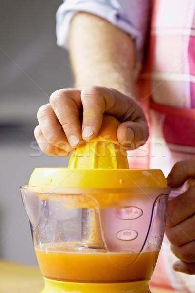 man preparing orange juice at home Stock photo © diego_cervo
