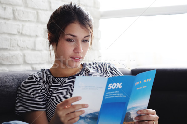 Woman Reading Travel Flye On Sofa At Home Stock photo © diego_cervo