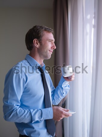 Businessman drinking coffee and looking out of window Stock photo © diego_cervo