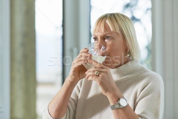 Portrait of senior woman having breakfast with milk Stock photo © diego_cervo