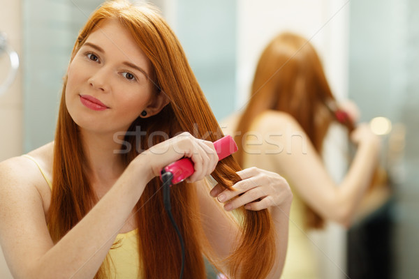 Beautiful Woman Ironing Healthy Red Hair With Iron Straightener Stock photo © diego_cervo