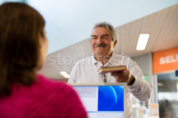 girl and senior man returning book in library Stock photo © diego_cervo