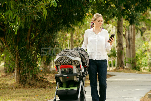 Mother With Baby In Pushchair Typing Message On Phone Stock photo © diego_cervo