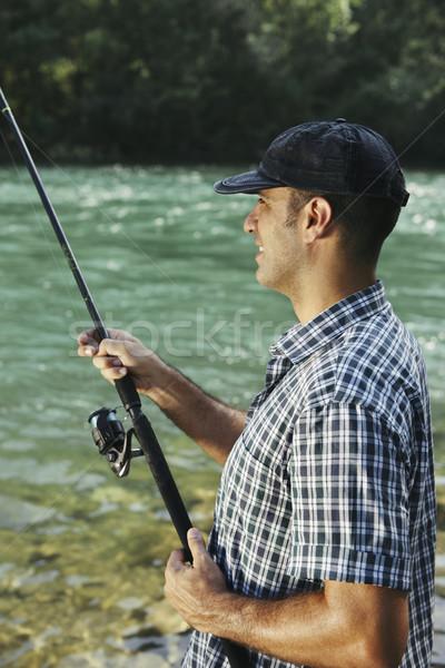 Pêcheur permanent rivière canne à pêche adulte Photo stock © diego_cervo