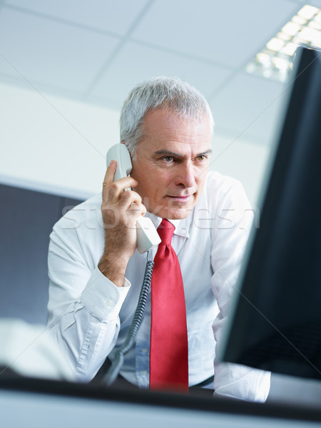Stock photo: mature businessman on the phone in office