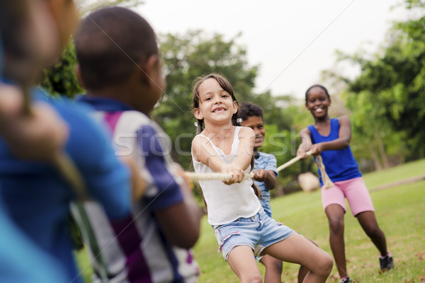 Happy school children playing tug of war with rope in park Stock photo © diego_cervo