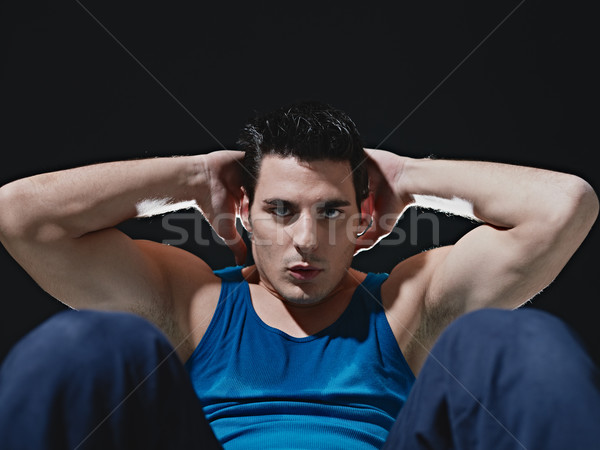Stock photo: man doing series of sit-ups on black background