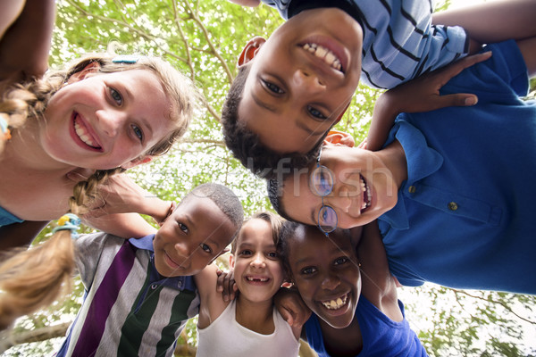 Stock photo: Children embracing in circle around the camera and smiling