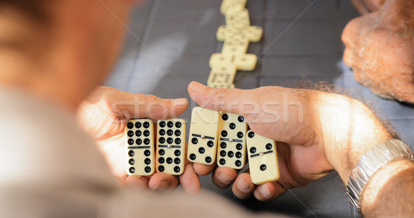 Gepensioneerd senior man spelen domino spel Stockfoto © diego_cervo